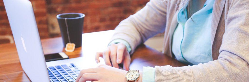 Man met thee en macbook aan het studeren.