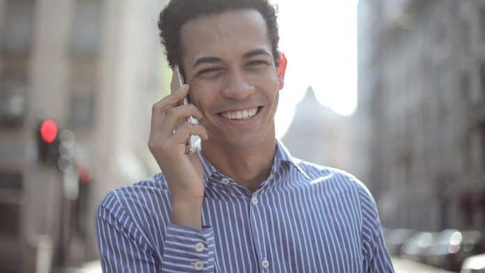 Man in overhemd aan telefoon