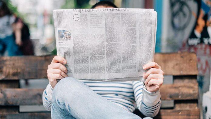 man leest krant op bankje