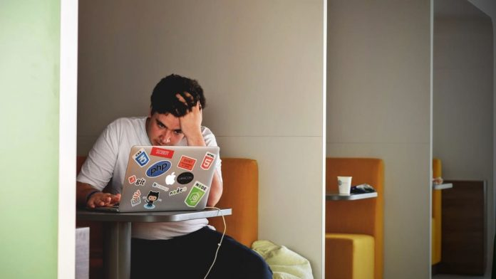 Man achter laptop verveeld