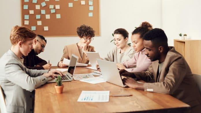 mensen werken gezamenlijk aan bureau met laptops